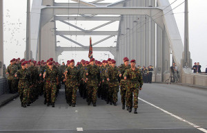 Soldiers from The 2nd Battalion The Parachute Regiment line the bridge in Arnhem (John Frost Bridge) and have a small memorial ceremony.   Today was the 65th anniversary commemorations of Operation Market Garden, one of the most notable military operations of World War 2, which was held at Arnhem in the Netherlands.  At 7am 2 PARA marched onto John Frost Bridge, the famous ' Bridge Too Far' to hold a memorial service. It is named after the then Commanding Officer of 2 PARA. Following the service there was the annual service at Oosterbeek cemetery attended by veterans and their families. This year Secretary of State for Defence Bob Ainsworth laid a wreath at the memorial. At the end of the service around 700 local Dutch children laid flowers on each of the graves at the cemetery.